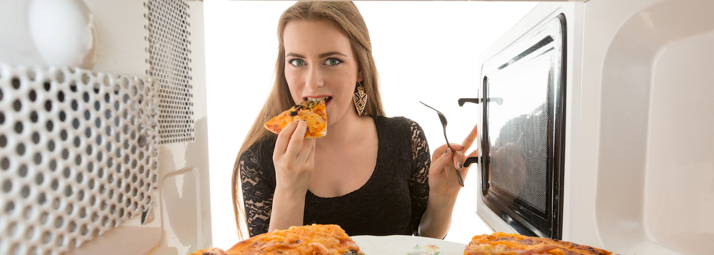 Woman taking reheated pizza from microwave